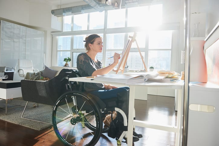Law Office of Tipton-Downie Caucasian woman in wheelchair painting on easel
